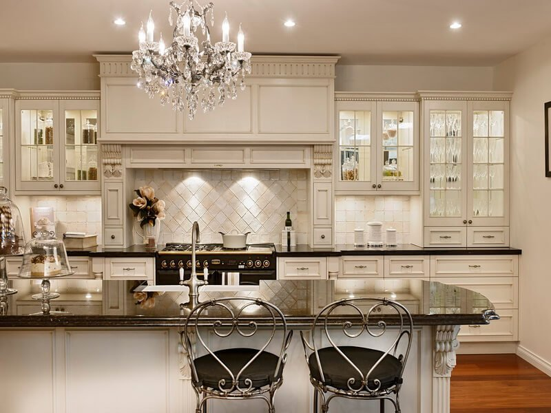 awesome-french-country-kitchen-with-luxurious-chandelier-above-dark-glass-top-kitchen-island-and-artistic-stools
