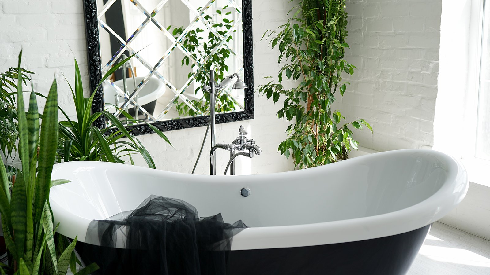 Bathtub and green plants in bathroom interior in luxury home