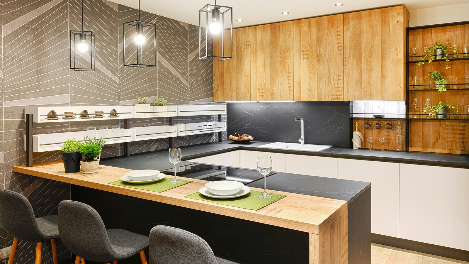 Modern fitted kitchen interior with appliances and bar counter with place settings for dining and row of stools lit by hanging ceiling lights