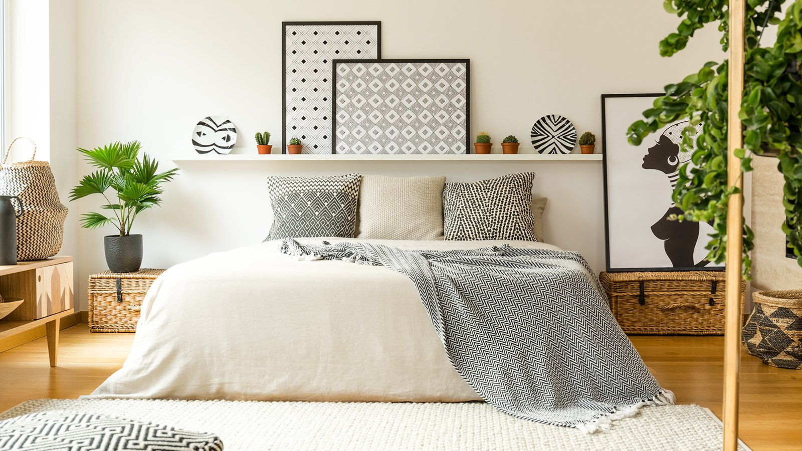 Warm bedroom interior with a comfy bed, patterned blanket and pillows, plants and modern graphics