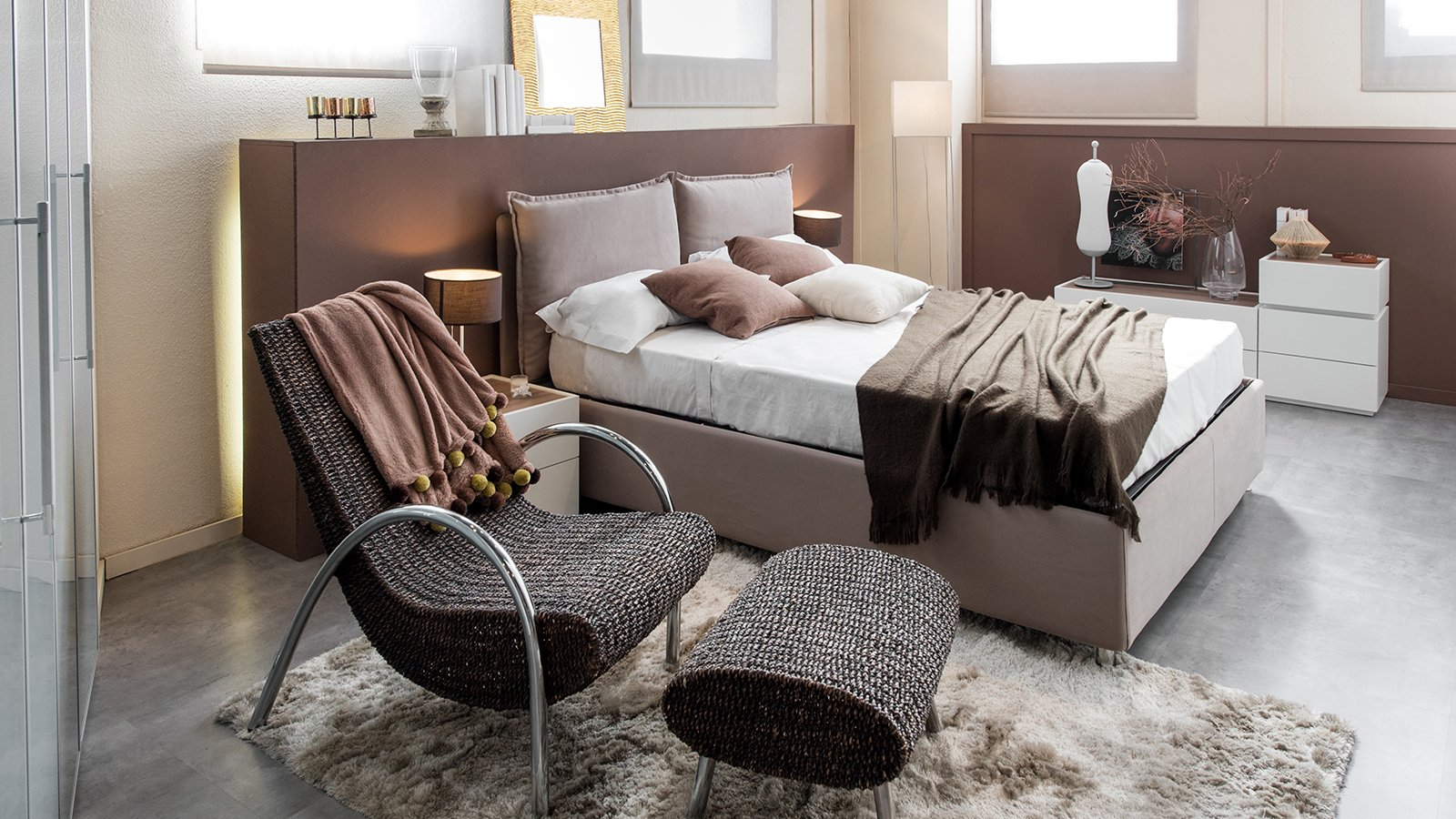 Modern luxury bedroom with recliner chair and double bed with large headboard and cabinets in brown decor