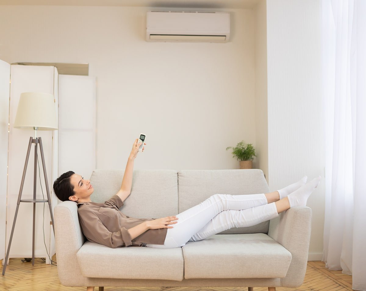 Woman turning on air conditioner