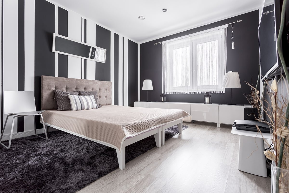 Luxury bedroom with black and white stripes painted on wall