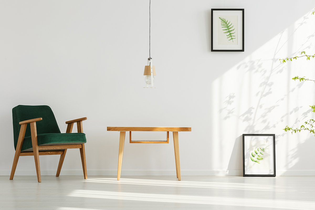 White home interior with green armchair, table, lamp, leaf posters