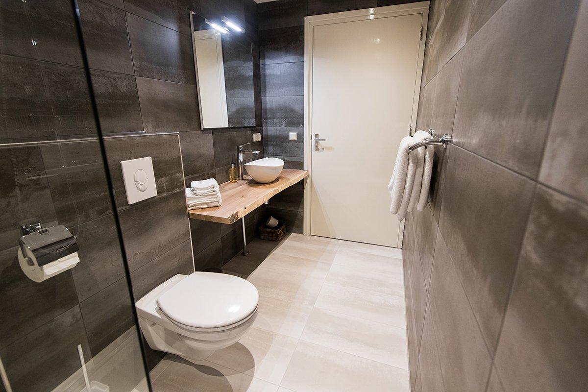 Large dark stone tiles in bathroom