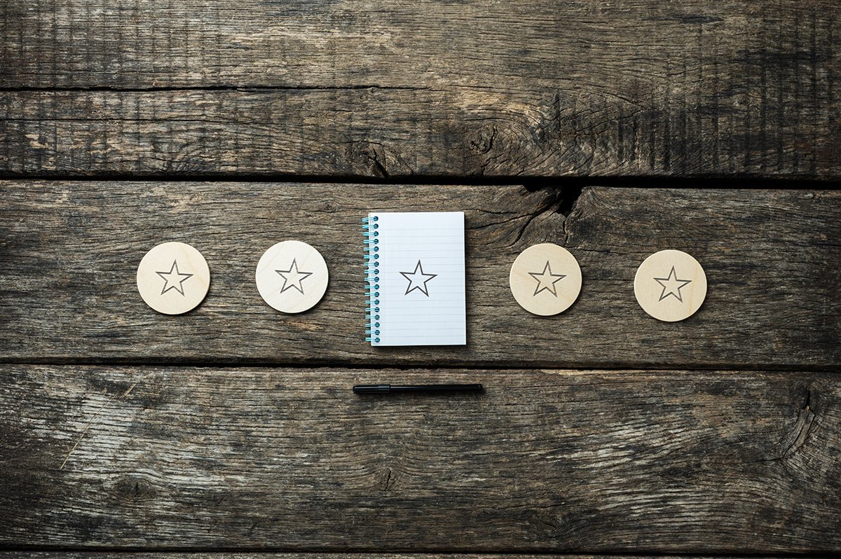 Five stars drawn on wooden cut circles and notepad, with black pen lying around. Over rustic wooden background.