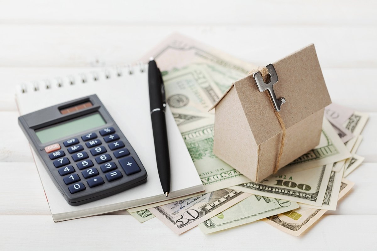 Model of cardboard house with key, calculator, notebook, pen and cash dollars. House building, loan, real estate. Cost of public utilities, insurance, rent or buying a new home concept