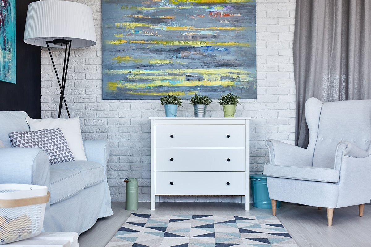 Pastel living room with sofa, armchair, chest of drawers and painting