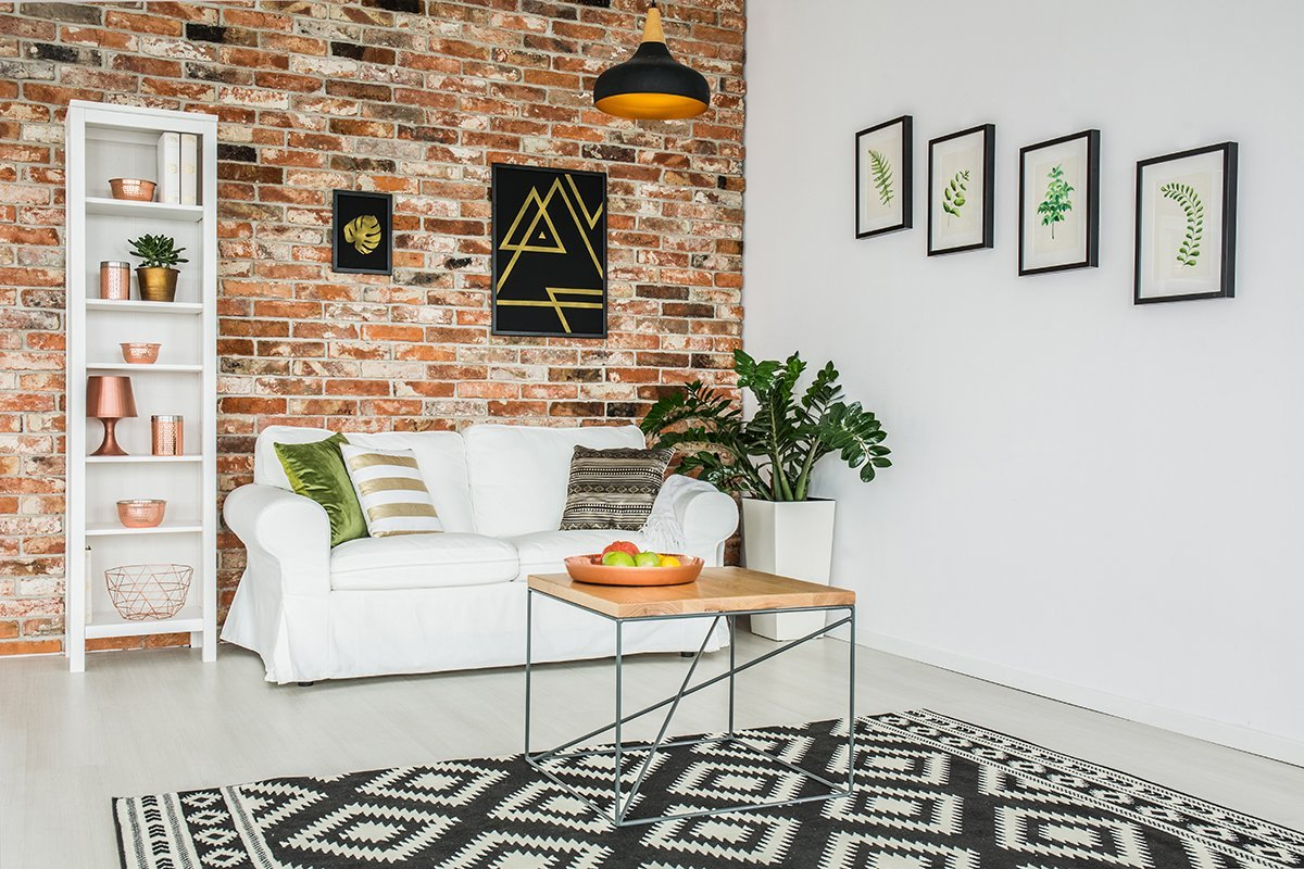 Stylish cozy living room with red brick wall and white sofa
