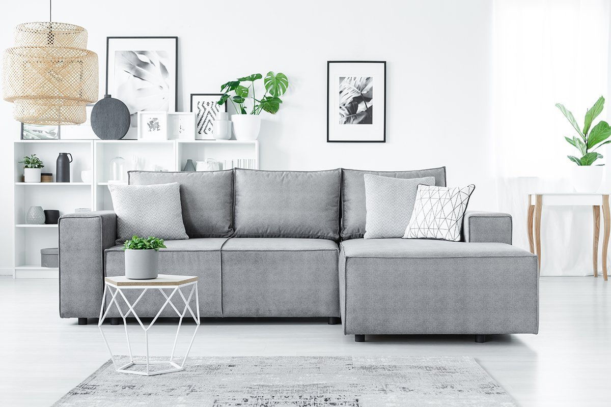Big, corner sofa with pillows, white shelves and plants in a modern living room interior