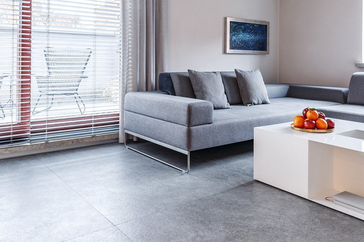 Grey corner couch and white table in bright living room interior with plants and view on the terrace