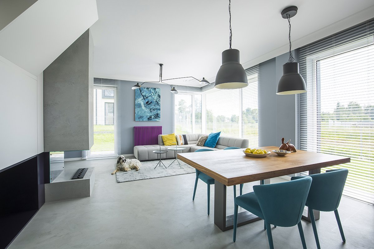 Lamps above wooden table and armchairs in spacious apartment interior with corner sofa and dog