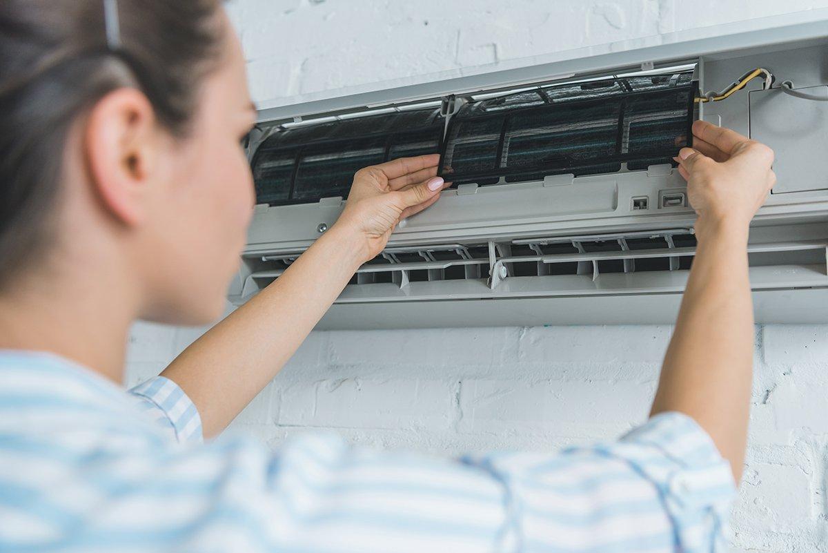 selective focus of female worker repairing air conditioner