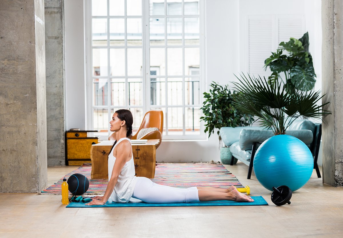 Ahtletic beautiful woman training at home - Young girl doing fitness in her apartment, concepts about fitness, sport and health