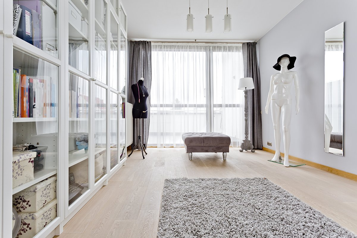 Well lighted walk-in closet with rack, wide window and two lay figures