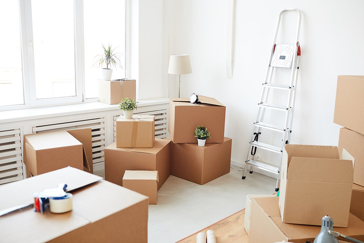 Wide angle background of stacked cardboard boxes in empty white room, moving, relocation and house decor concept
