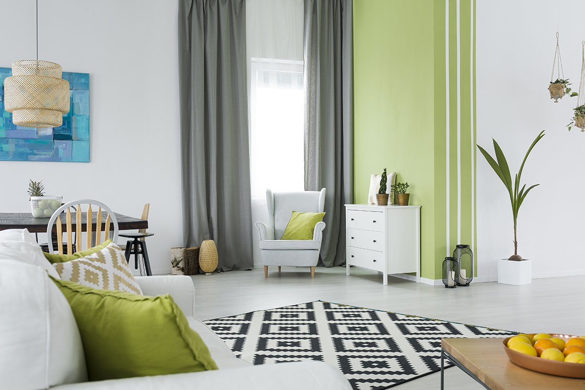 Green and white home interior with sofa, armchair, dresser, table