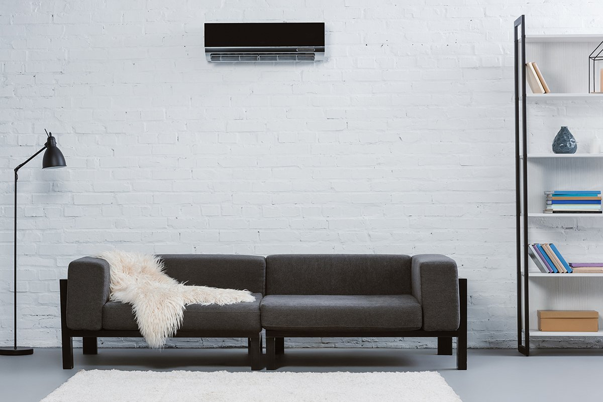 Modern air conditioner hanging on white brick wall at living room