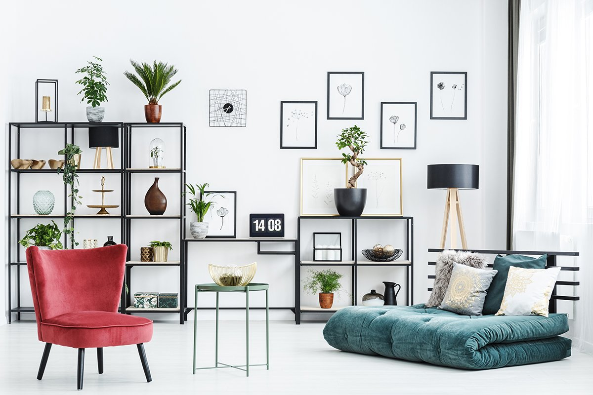 Table between red chair and green futon in home office interior with posters and plants