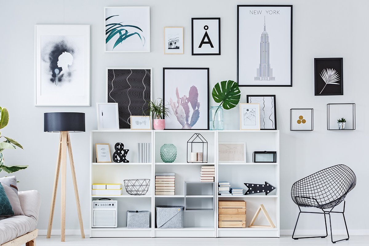 Wooden shelves with decorations, boxes and books in white living room interior with fresh plants and modern art posters