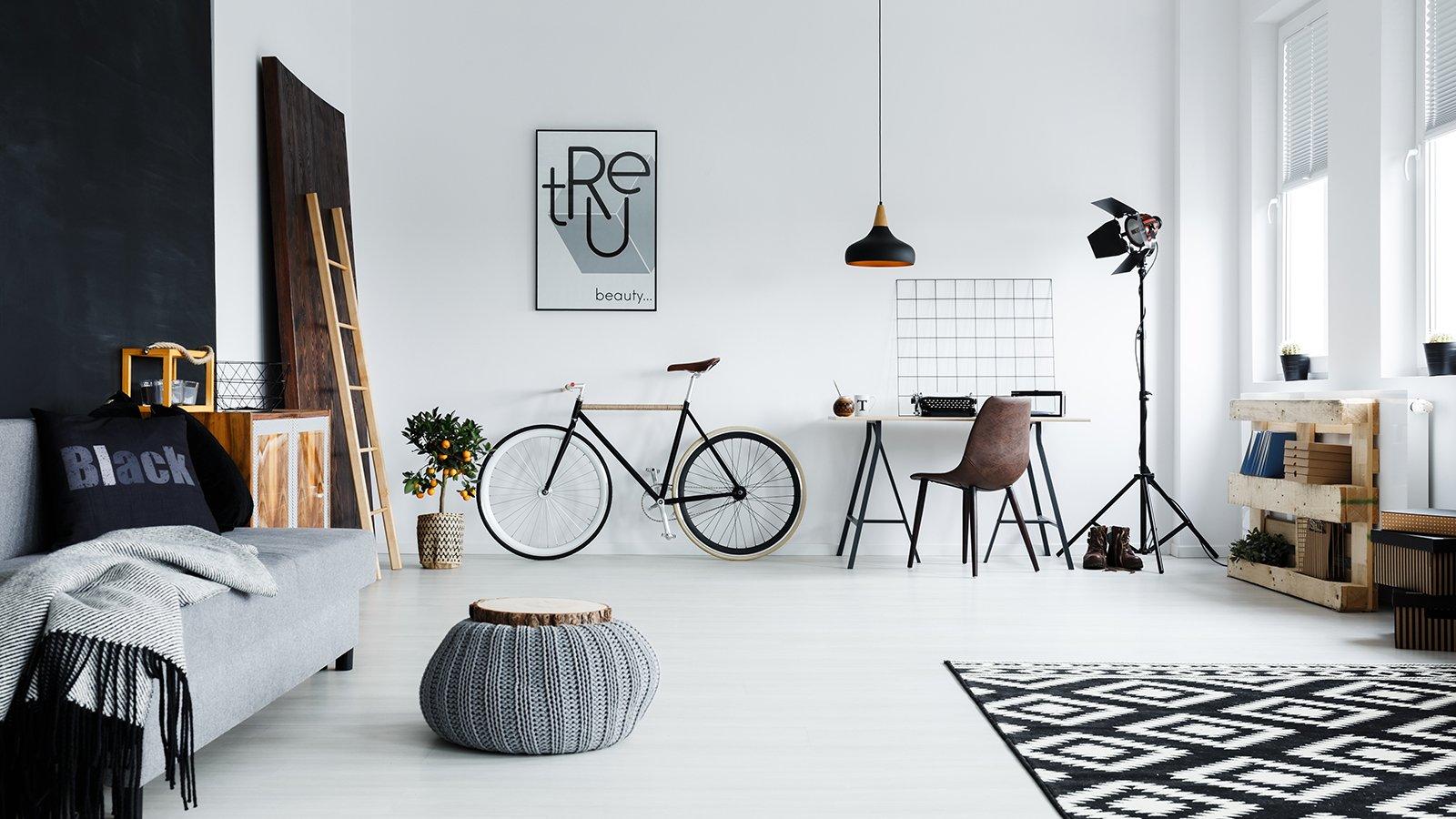Modern spacious studio apartment with sofa, bike and desk